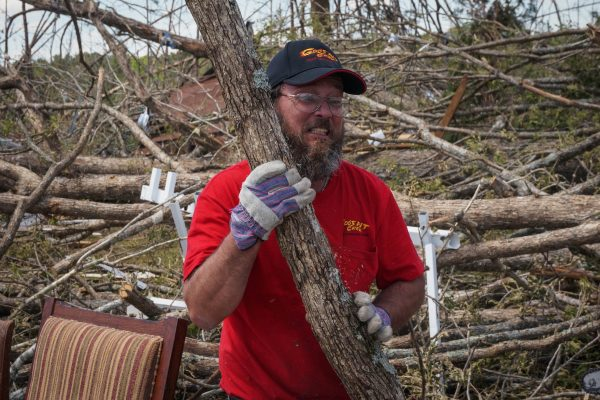 GPC Voluneer Dan Deboe helps clear branches and debris after a tornado in Louisville, MS.