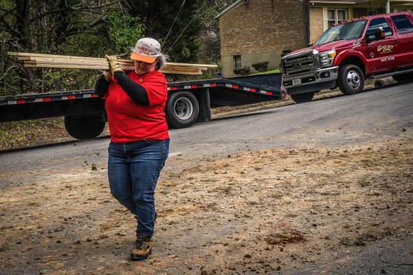 GPC volunteer Tricia Waller carries lumber to volunteers who are helping to tarp the roof of a damaged home, after a tornado in Danville, Virginia.