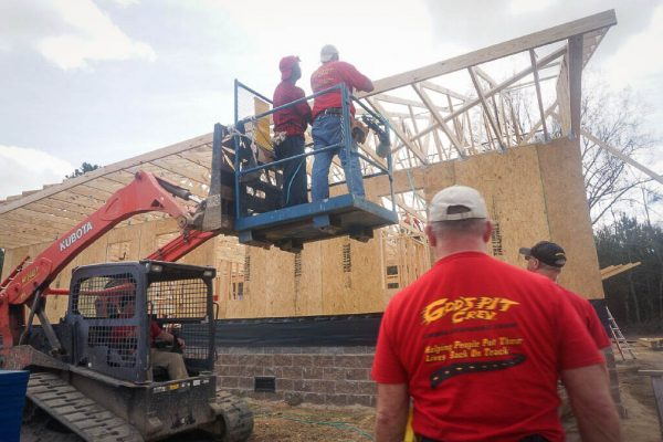 Volunteers work to install roof beams during a home rebuild project.