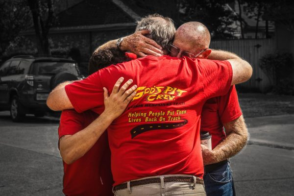 After seeing a family's reaction to their renovated home in Houston, Texas, a group of volunteers embrace each other as they are overcome with emotion.